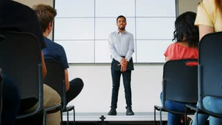 High School Students Applaud Male Teacher Giving Presentation In Front Of Screen