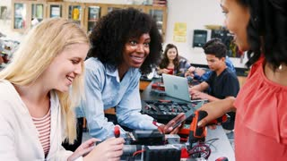 High School Teacher With Female Pupils Building Robotic Vehicle In Science Lesson