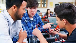 High School Teacher With Male Pupils Building Robotic Vehicle In Science Lesson