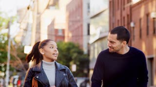 Hispanic couple walking hand in hand in the street, close up