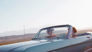 Laughing female friends driving in convertible on a highway