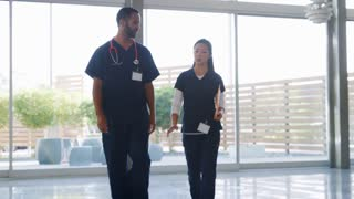 Male doctor and female nurse walk to the camera in hospital