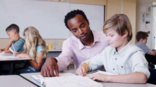 Male elementary school teacher working in class with boy