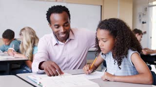 Male elementary school teacher working in class with girl