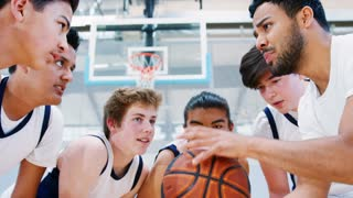 Male High School Basketball Players Joining Hands On Ball During Team Talk With Coach