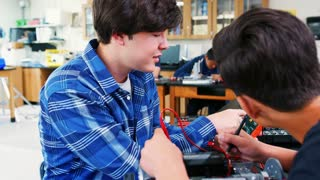 Male High School Pupils Building Robotic Vehicle In Science Lesson