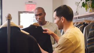 Male shop assistant helping customer in a men�s clothes shop