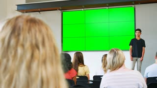 Male Student Giving Presentation To High School Class In Front Of Screen