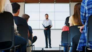 Male Teacher Giving Presentation To High School Class In Front Of Screen