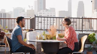 Man Giving Woman Gift As They Celebrate On Rooftop Terrace With City Skyline In Background