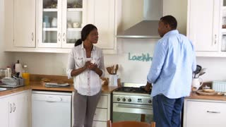 Mature Couple Chat In Kitchen As Man Prepares Meal In Kitchen