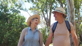 Mature Couple Walking Along Forest Path Together