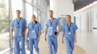 Medical Interns Wearing Scrubs Walk Towards Camera in Busy Hospital