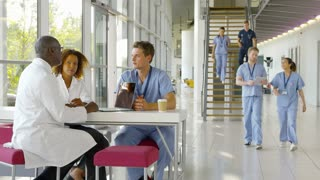 Medical Team Meeting Around Table In Busy Hospital