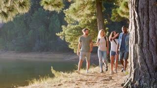 Men Giving Women Piggybacks As They Walk Beside Lake Together