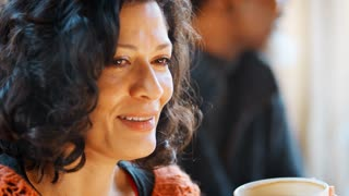 Middle Aged Woman Meeting Friends Around Table In Coffee Shop
