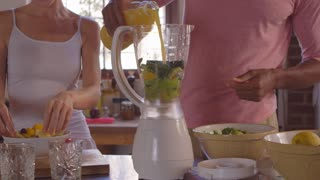 Mixed race couple making smoothies using blender, close up, shot on R3D