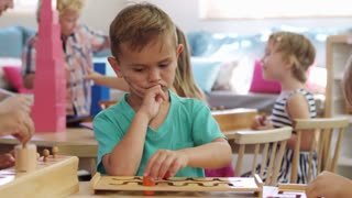 Montessori Pupil Working At Desk With Wooden Shape Puzzle