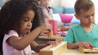 Montessori Pupils Working At Desk With Wooden Shape Puzzles