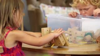Montessori School Pupils Work At Desk With Wooden Building Set