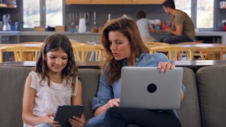 Mother And Daughter Sitting On Lounge Sofa Using Digital Devices