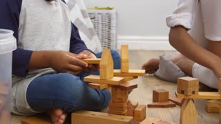 Mother And Son Playing With Building Blocks In Bedroom