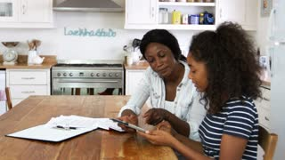 Mother Helps Teenage Daughter With Homework Using Digital Tablet