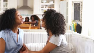 Mother Talking With Teenage Daughter Sitting On Sofa Together
