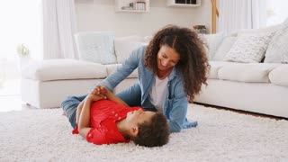 Mother Tickling Son As They Play Game In Lounge Together