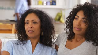 Mother With Teenage Daughter Sits On Sofa Watching TV Together
