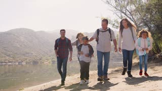 Multi generation family hiking by a mountain lake