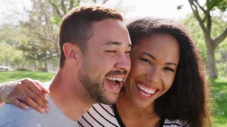 Outdoor Head And Shoulders Portrait Of Smiling Couple In Park
