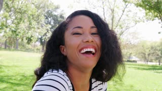 Outdoor Head And Shoulders Portrait Of Smiling Young Woman In Park