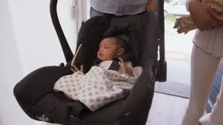 Parents Arriving Home With Newborn Baby In Car Seat