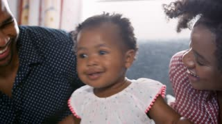 Parents Singing And Dancing With Baby Daughter At Home