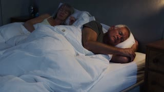 Peaceful Senior Couple Asleep In Bed At Night