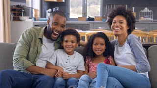 Portrait Of Family On Sofa In Open Plan Laughing Towards Camera