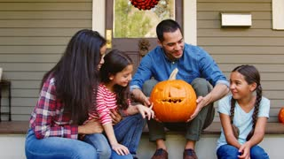 Portrait Of Family With Carved Halloween Pumpkin On House Steps