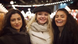 Portrait Of Female Friends Enjoying Christmas Market At Night