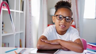 Portrait Of Girl Wearing Glasses Sitting At Desk In Bedroom Using Digital Tablet