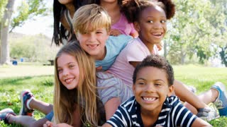 Portrait Of Group Of Children With Friends Having Fun In Park Shot In Slow Motion