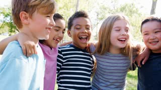 Portrait Of Group Of Children With Friends In Park Shot In Slow Motion