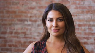Portrait Of Smiling Hispanic Woman Standing Against Brick Wall In Coffee Shop