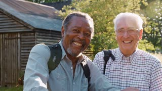 Portrait Of Two Male Senior Friends Hiking In Countryside