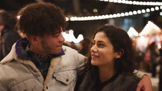 Portrait Of Young Couple Enjoying Christmas Market At Night
