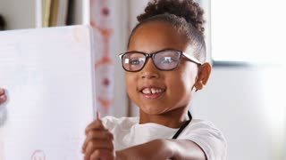 Portrait Of Young Girl Wearing Glasses With Drawing In Bedroom