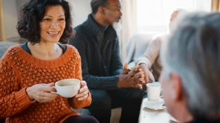 Pull Focus Shot Of Middle Aged Friends Meeting In Coffee Shop