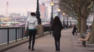Rear View Of Couple Walking Along South Bank On Visit To London