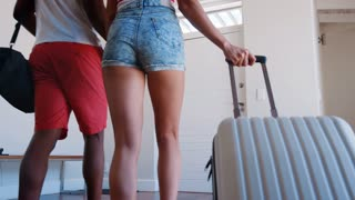 Rear View Of Couple With Luggage Leaving Home For Vacation