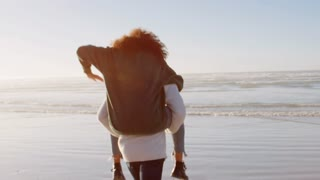 Rear View Of Man Giving Woman Piggyback On Winter Beach Vacation